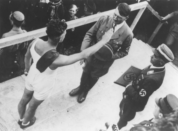 Берлин, 1936 год: Адольф Гитлер приветствует немецких олимпийцев