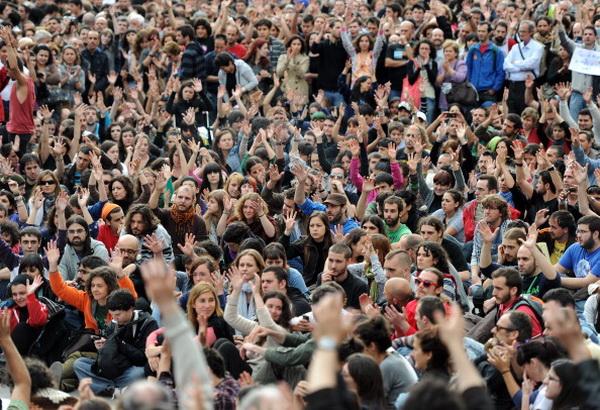 """"""" безработица сильно ударила по молодым поколениям, которые не знали эпохи франкистской диктатуры и которые выстроили своё политическое воображение в уже демократической Испании. Эта молодёжь просигнализировала своё «возмущение» в 2011 году на улицах"""" На фото: манифестация на площади Пуэрта дель Соль (Puerta del Sol) в центре Мадрида 20 мая 2011 года"""