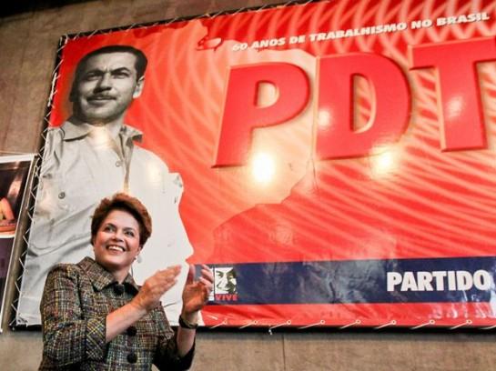 Президент Бразилии и один из лидеров Партии трудящихся Дилма Руссеф на фоне плаката ДТП