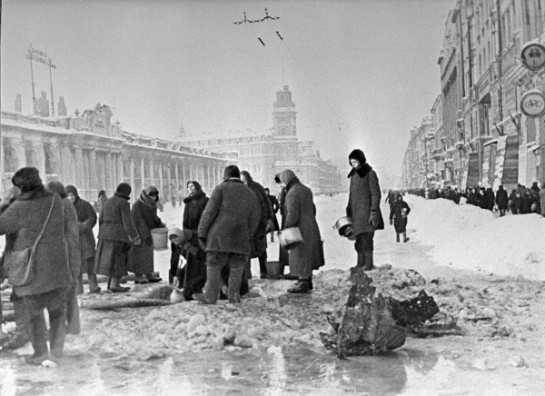 Жители блокадного Ленинграда набирают воду, появившуюся после артобстрела в пробоинах в асфальте на Невском проспекте, фото Б. П. Кудоярова, декабрь 1941 года