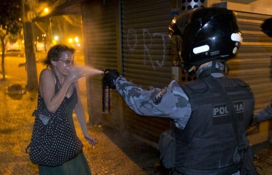 В Бразилии проходят крупнейшие волнения за последние 20 лет. Граждане не хотят, чтобы за их счёт государство оплачивало «футбольные стройки». На фото: полицейский распыляет перечный газ в лицо женщине во время демонстрации в Рио-де-Жанейро. (©AP Photo / Victor Р. Caivano)