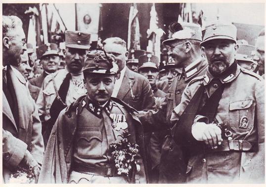 13 мая 1932 года канцлером Австрии был избран связанный с хеймвером Энгельберт Дольфус (в центре). Он противостоял гитлеровским планам по поглощению Австрии Германией. Дольфуса, как и хеймвер, привлекал итальянский фашизм