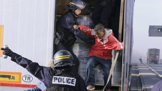 Французские полицейские в Кале вытаскивают спрятавшегося в грузовике мигранта. REUTERS/Pascal Rossignol