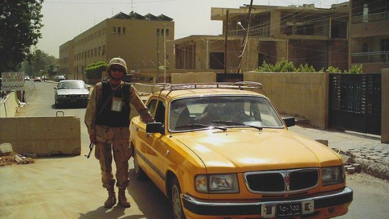Американский солдат фотографируется с местной достопримечательностью - автомобилем ГАЗ