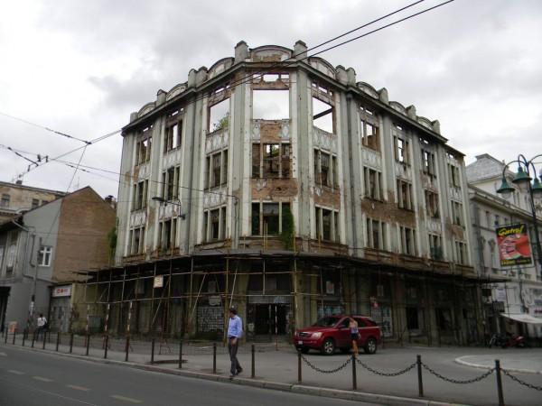 Стены домов испещрены следами от обстрелов. Здание за кафедральным католическим собором Святого Сердца Иисуса всё ещё не восстановлено после того, как было разрушено во время осады Сараево