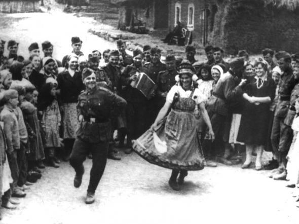 По мнению историка Сергея Дробязко, при минимальном контроле со стороны немецкой администрации Локотское самоуправление добилось крупных успехов в социально-экономической жизни округа / На фото: боец РОНА исполняет русский танец в окружении жительниц Локотского округа