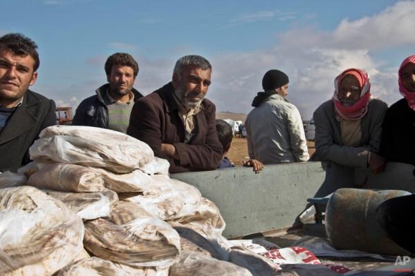 """""""Сейчас мы не можем создать ситуацию, в которой каждый имеет возможность трудиться, где специалисты могут получить работу"""" / На фото: раздача хлеба жителям Кобани / AP Photo / Jake Simkin"""
