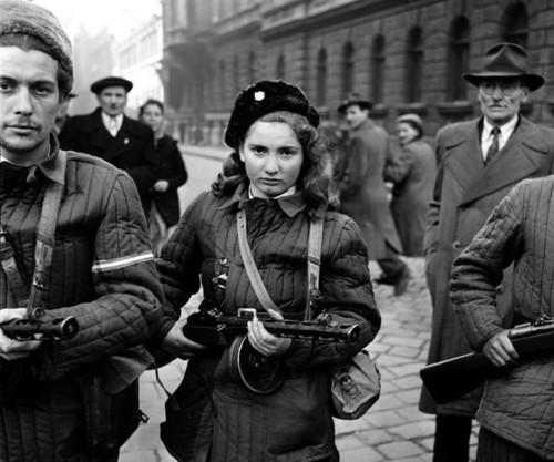 Образ одного из этих ватников обошёл весь мир. Точнее, одной из них. Знакомьтесь: Эрика Корнелия Селеш. Еврейка. Отец - жертва Холокоста, мать - убеждённая коммунистка. Работала помощницей гостиничного повара. В дни революции ей было 15 лет